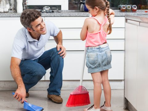 Father and daughter cleaning in the kitchen, sweep floor at home, man little girl family